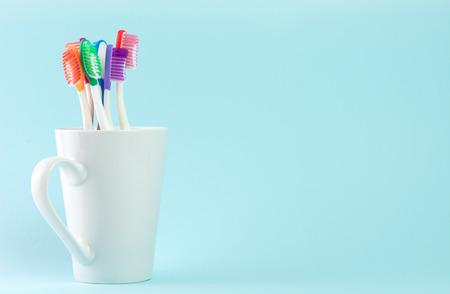 Foto de Multicolor toothbrushes in white mug, with copyspace - Imagen libre de derechos