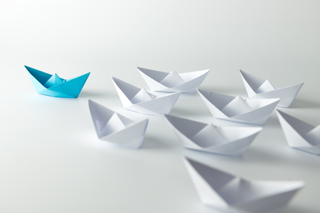 Foto de Leadership concept with blue paper ship leading among white - Imagen libre de derechos