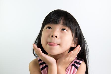 Foto für Asian child shows delicious expression with tongue out - Lizenzfreies Bild