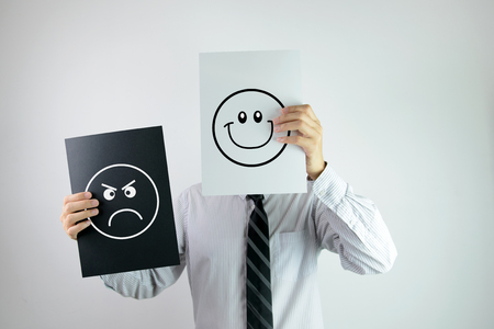 Photo pour Businessman holding two papers with happy and angry face each on them - image libre de droit