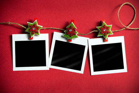 Photo pour Christmas polaroid photo frames hanging on rope over red background - image libre de droit