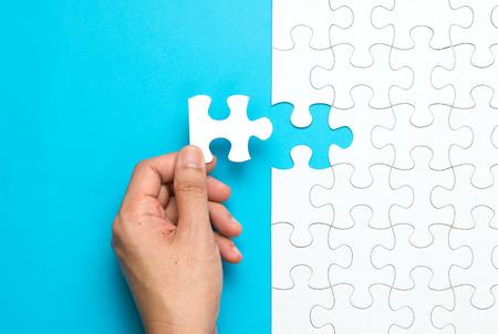 Photo pour Hand put the last piece of jigsaw puzzle to complete the mission - image libre de droit