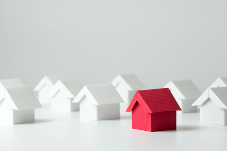 Photo pour Red house in among white houses for real estate property industry - image libre de droit