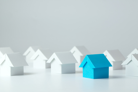 Blue house in among white houses for real estate property industry
