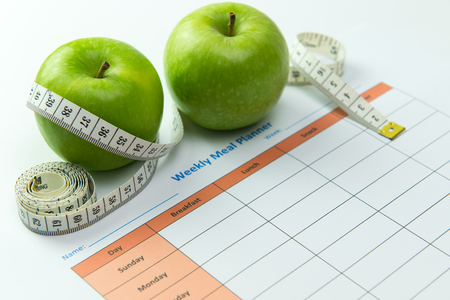 Photo for Weekly meal planner with green apples and tape measurement - Royalty Free Image