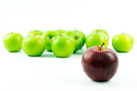 Photo pour Red apple standing out among the green apples over white background - image libre de droit