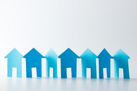 Photo pour Blue paper houses in a row on white background - image libre de droit