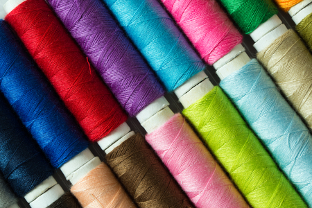 Close up of various colored threads forming background