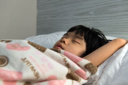 Close up of Asian child sleeping soundly on bed