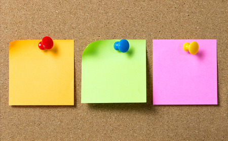 Foto de Three colors sticky notes paper attached to cork board using thumb tack pin - Imagen libre de derechos