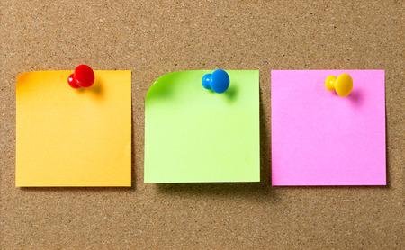 Foto de Three colors sticky notes paper attached to cork board using thumb tack pin - Imagen libre de derechos