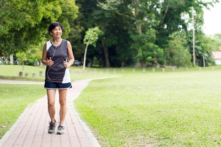 Foto de Front view of senior Asian woman jogging through park - Imagen libre de derechos