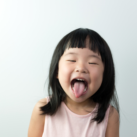 Photo pour Happy little asian girl with funny face isolated on white background - image libre de droit