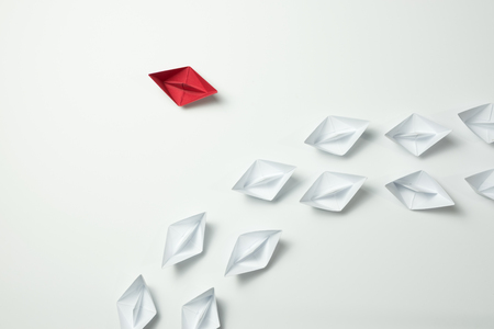 Photo for Red paper ship changing direction and white ones. New idea, change, trend, courage, creative solution, innovation and unique way concept. - Royalty Free Image