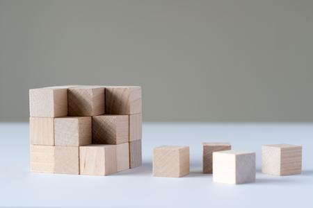 Photo pour Wood cubes to complete a bigger square block - image libre de droit