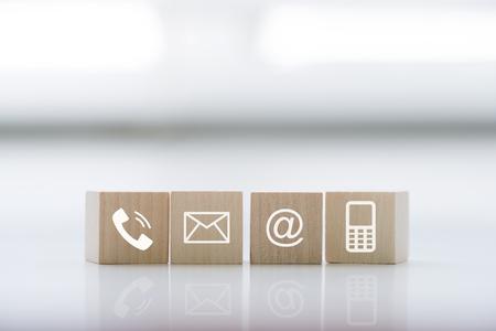 Foto de Contact us concept with wood block symbol telephone, mail, address and mobile phone. Website page contact us or e-mail marketing concept - Imagen libre de derechos