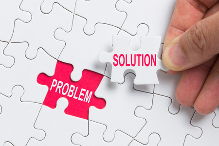 Photo for Hand holding piece of white jigsaw puzzle with word problem and solution. - Royalty Free Image