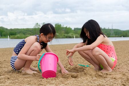 Photo for Two little Asian girls playing sand at beach with bucket and spade - Royalty Free Image