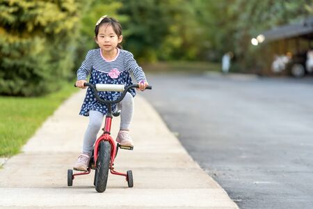 Photo for Cute little Asian girl learning ride a bicycle without wearing a helmet - Royalty Free Image