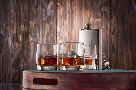Photo pour Two round glasses of whiskey on the rocks and a metal flask stand on a tray against an old wooden wall. Low key. - image libre de droit