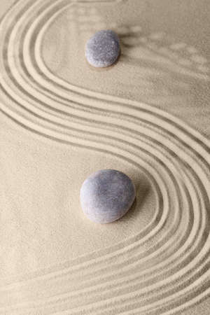 Photo pour Smooth lines on the sand and round stones in the rock garden, for relaxation and spiritual harmony. Zen garden of meditation, relaxation, restoration of balance and harmony of spirituality, relaxation - image libre de droit