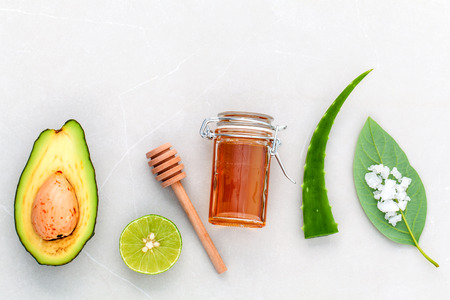 Alternative skin care  and scrub fresh  avocado , leaves ,sea salt , oils, lime and honey on marble background.