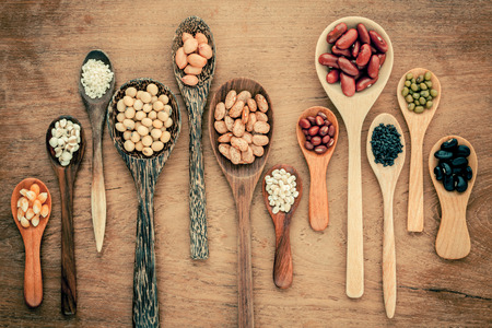 Assortment of beans and lentils in wooden spoon on teak wood background. mung bean, groundnut, soybean, red kidney bean , black bean ,sesame, corn ,red bean and brown pinto beans .