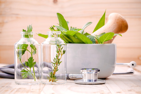Alternative health care fresh herbal in laboratory glassware  with  stethoscope on wooden background.