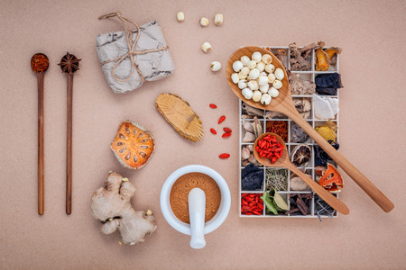 Foto de Alternative health care dried various Chinese herbs in wooden box , dried quince ,ginger and lotus seed in wooden spoon with mortar on brown background. - Imagen libre de derechos