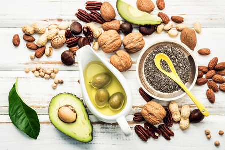 Foto de Selection food sources of omega 3 and unsaturated fats. Superfood high vitamin e and dietary fiber for healthy food. Almond ,pecan,hazelnuts,walnuts and olive oil on stone background. - Imagen libre de derechos