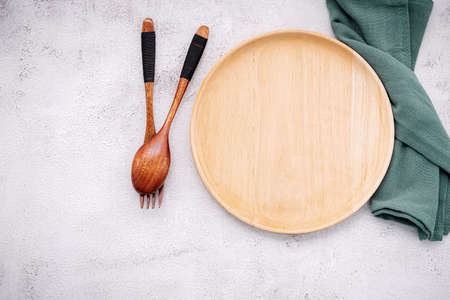 Photo pour Food conceptual image of wooden plate with spoon and fork on white concrete background. - image libre de droit