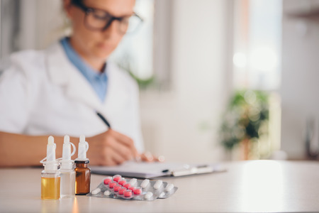 Photo pour Medical supplies on table and doctor in the background writing prescription - image libre de droit