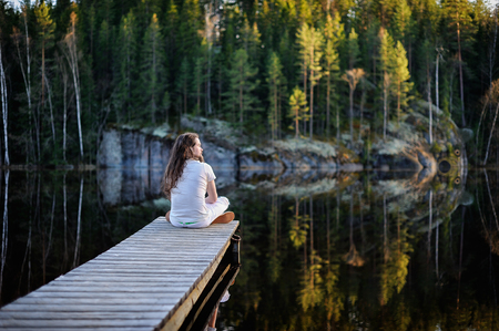 Photo for Traveler man sitting and meditating on a pontoon by a lake at the morning - Royalty Free Image