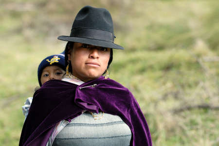 the latin woman in national clothes with little child. ecuador. south america