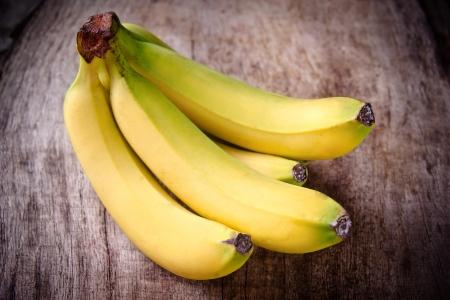Freshly harvested bananas on wooden background
