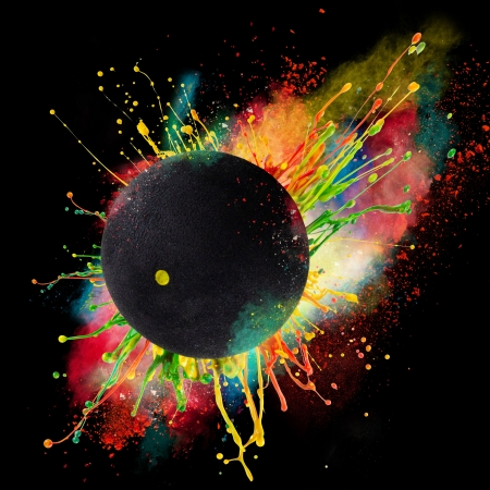 Colorful paint splashing with squash ball isolated on black