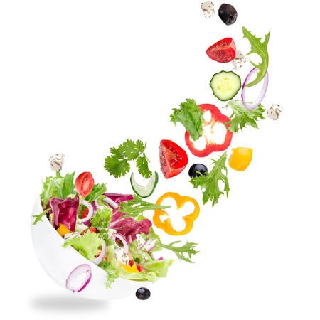 Foto de Fresh salad with flying vegetables ingredients isolated on a white background. - Imagen libre de derechos