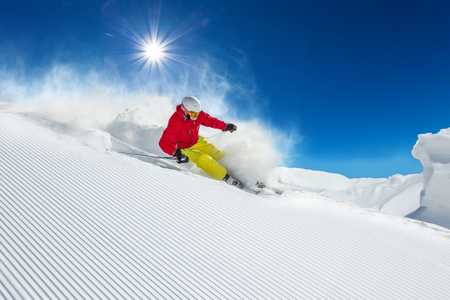 Skier skiing downhill during sunny day in high mountainsの写真素材