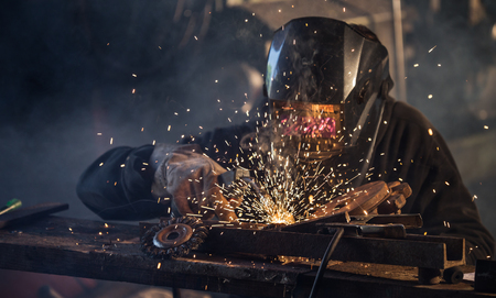 Working welder in action with bright sparks.