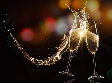 Glasses of champagne with splash, isolated on black