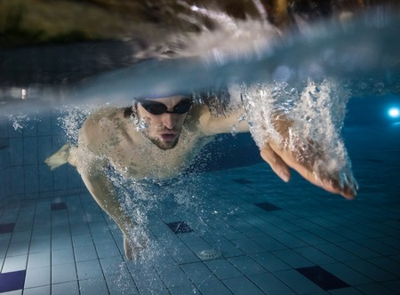 Photo pour Male swimmer at the swimming pool. Underwater photo. - image libre de droit