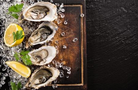 Foto de Fresh oysters on a black stone plate top view - Imagen libre de derechos