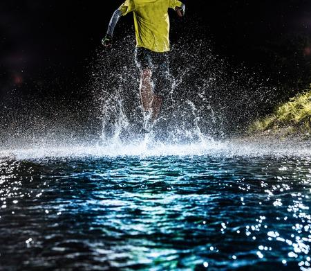 Single runner running, making splash in a stream during night.