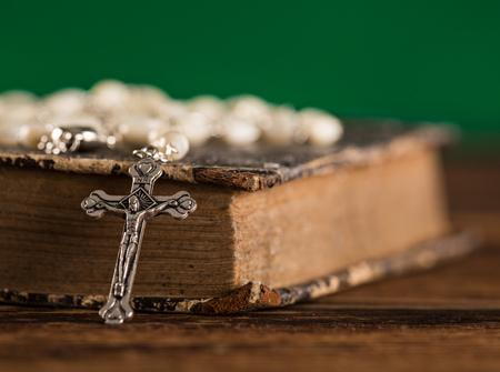 Closeup of iron Christian cross with holy Bible.