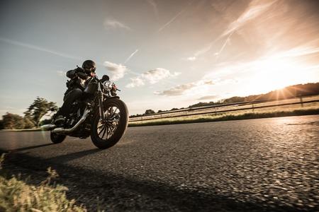 Photo pour Man riding sportster motorcycle during sunset. - image libre de droit