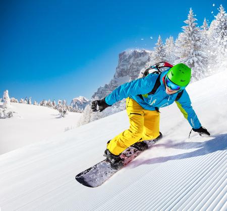 Foto de Active man snowboarder riding on slope, snowboarding closeup. - Imagen libre de derechos