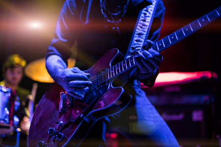 Photo pour A rocker is playing guitar on stage. - image libre de droit