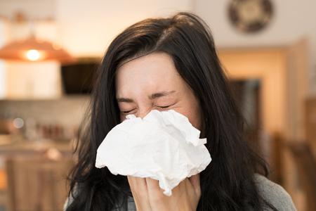 Young woman having flu, blowing her nose.