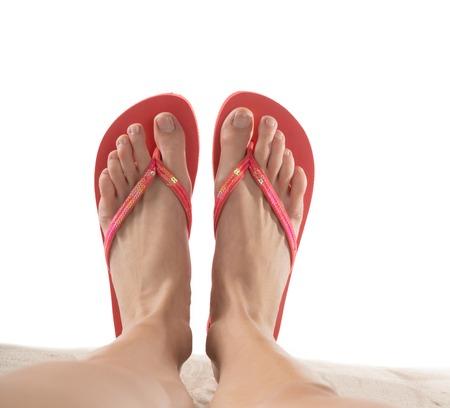 Foto de Female legs with flip-flops isolated on white background. - Imagen libre de derechos
