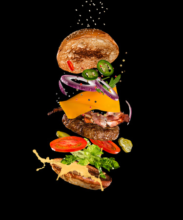 Photo pour Tasty hamburger with flying ingredients on dark background - image libre de droit